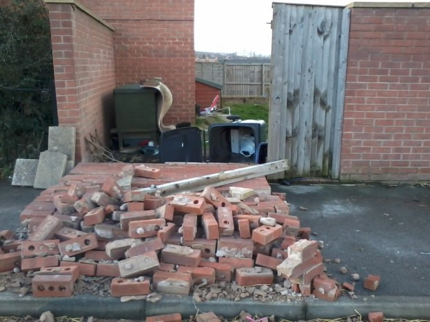 brick wall fallen onto pavement